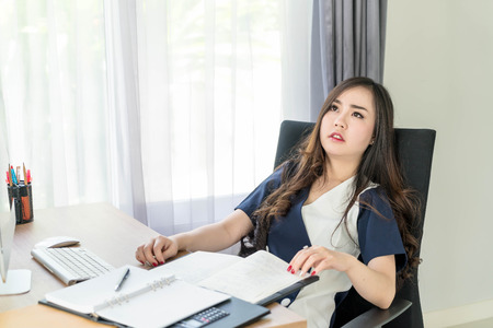 agressive: seriously asian woman in office - business concept