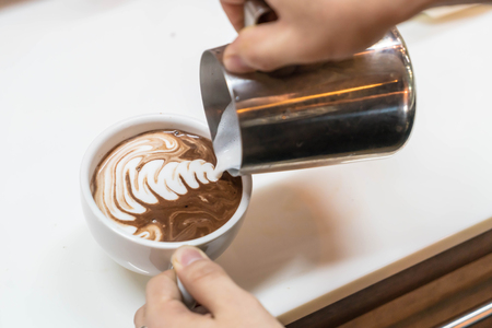 pouring milk in cup to male art latte Stock Photo