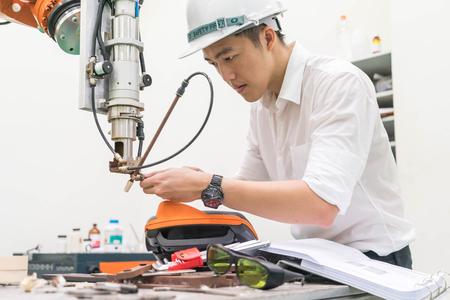 Ingeniero eléctrico trabajando con una máquina de robot Foto de archivo - 84607277