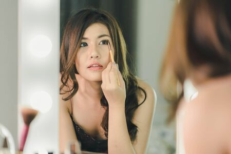 woman mirror: Young Beautiful Asian Woman making make-up near mirror - vintage effect filter