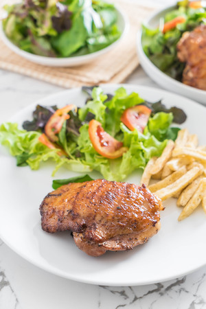 grill: grilled chicken steak with french fries and vegetable salad on plate Stock Photo