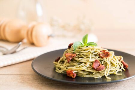 Spaghetti with basil pesto and bacon - Italian food style