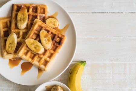 Banane gaufre au caramel sur plaque blanche Banque d'images - 89054281