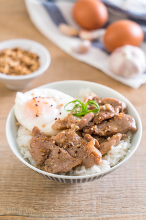 stir-fried pork with garlic on topped rice with egg - Asian food style Stock Photo