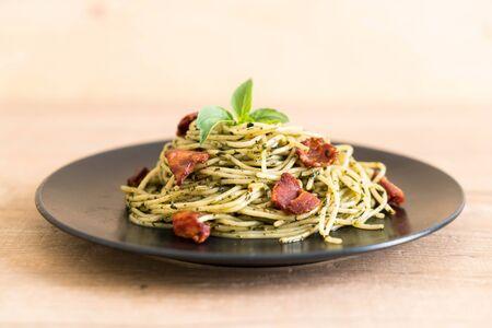 Spaghetti with basil pesto and bacon - Italian food style