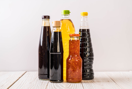 group of sauce bottle condiment for cooking on wood background Foto de archivo