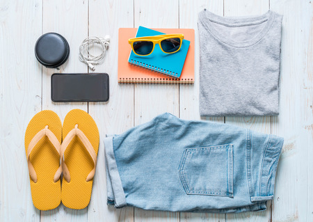 men's casual outfits of traveler, summer holiday on wood background