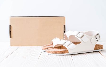 unisex leather sandals on wood background
