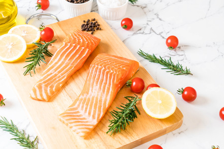 Raw salmon fillet with tomatoes lemon rosemary pepper and salt on wood board