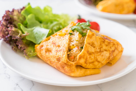 Flavored Fried Rice in an Omelet Wrapping with vegetable Stockfoto