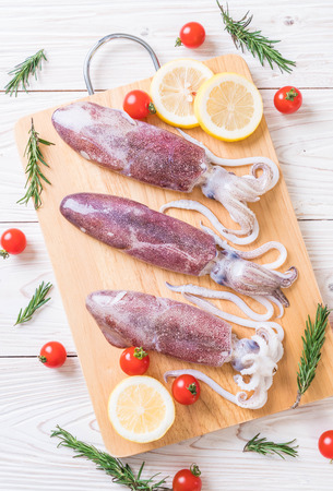 fresh octopus or squids raw on wooden board with ingredients Stock Photo