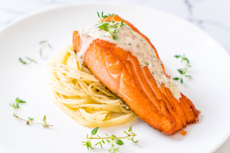 spaghetti with fried salmon on plate Stock Photo