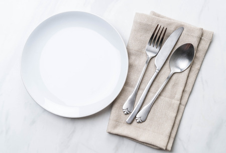 empty plate spoon fork and knife on table Stock Photo