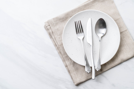 empty plate spoon fork and knife on table Stockfoto