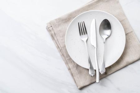 pusty talerz łyżka widelec i nóż na stole