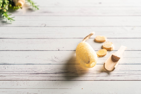 Cleansing Sponge with herbs on wood background