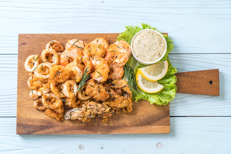 fried seafood (squids, shrimps, mussels) with sauce on wooden board