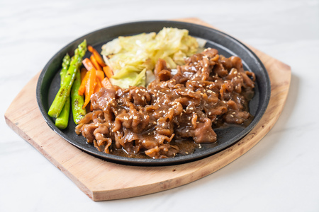 sliced pork steak on hot plate - Asian style Stock Photo