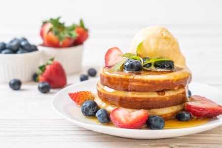 souffle pancake with blueberries, strawberries, honey and vanilla ice-cream Reklamní fotografie - 102427444