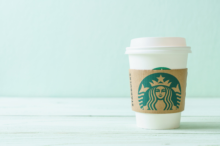 BANGKOK, THAILAND - JUN 5, 2018: White coffee cup with Starbucks logo on wood background. Starbucks is the worlds largest coffee house with over 20,000 stores in 61 countries.