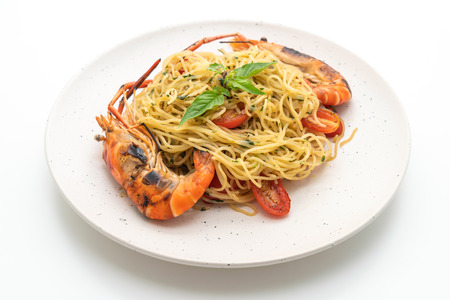 stir-fried spaghetti with grilled shrimps and tomatoes isolated on white background
