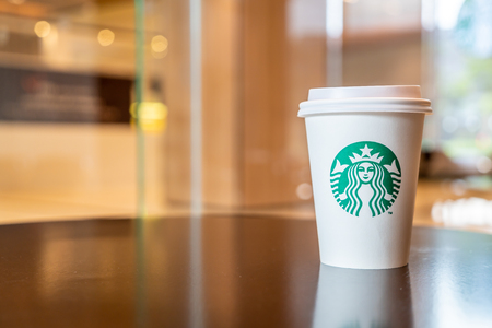 BANGKOK, THAILAND - June 29, 2018: Starbucks hot beverage coffee with holder on the table in Starbuck coffee shop.