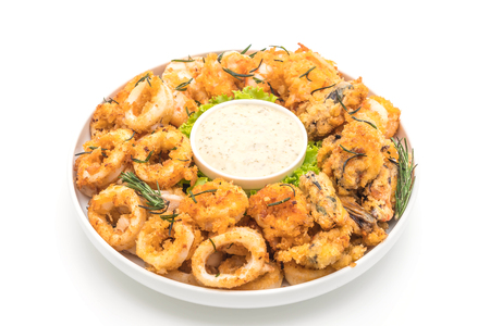 fried seafood (squids, shrimps, mussels) with sauce isolated on white background