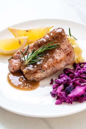 pork steak with red cabbage and mashed potatoes on white plate Фото со стока