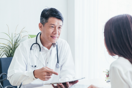 Asian doctor and patient are discussing something while sitting at the table Stockfoto