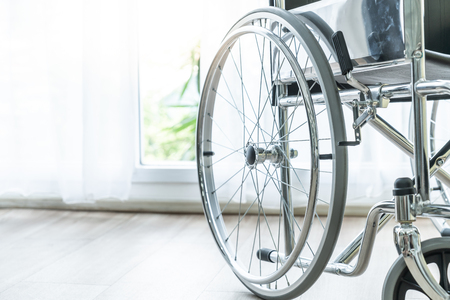 empty wheelchair in a room with curtain and sunlight