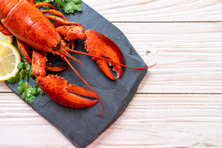 red lobster with vegetable and lemon on black slate plate Stockfoto