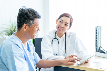 Asian Senior Patient Having Consultation With Doctor in Office  - selective focus point