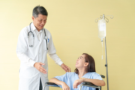 female patient on wheelchair talking with senior doctor Imagens