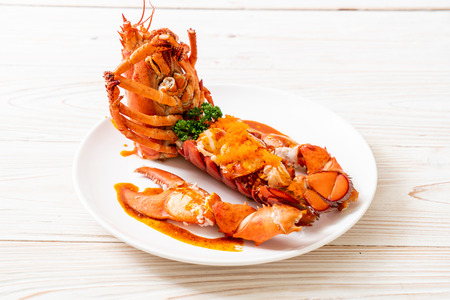 Lobster tail steak with sauce and shrimp eggs isolated on white background