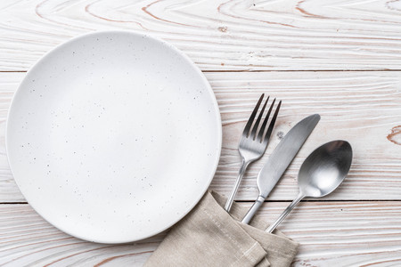 empty plate spoon fork and knife on table Imagens