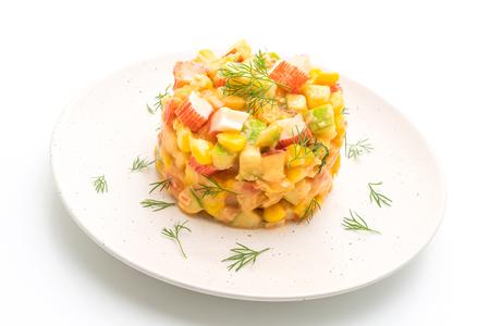 mixed fruit salad with crab stick (apple, corn, papaya, pineapple) isolated on white background