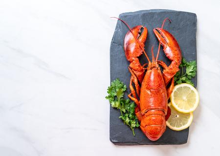 czerwony homar z warzywami i cytryną na czarnym łupkowym talerzu Zdjęcie Seryjne