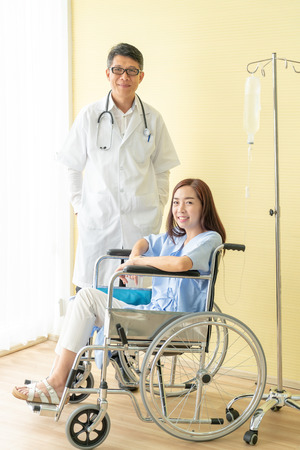 Asian female patient on wheelchair with senior doctor
