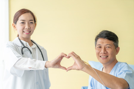Asian female doctor  smiling and make heart shave by hand with senior patient - selective focus point Standard-Bild