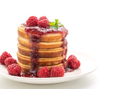 pancake with fresh raspberries and raspberry sauce isolated on white background