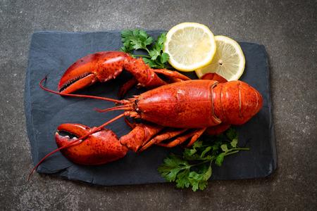 Homard rouge aux légumes et citron sur plaque d'ardoise noire