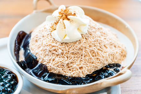 milk tea ice shave with black bubble and black grass jelly in cafe