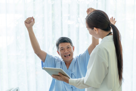 Asian senior patient on hospital bed discussing with female doctor - selective focus point