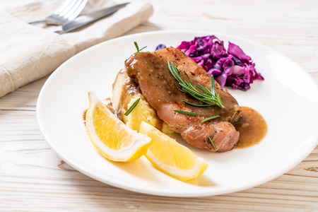 pork steak with red cabbage and mashed potatoes on white plate Imagens
