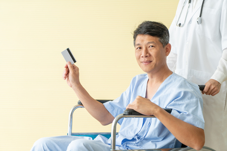 Asian senior patient wheelchair smiling with credit card - silective focus point Stock Photo