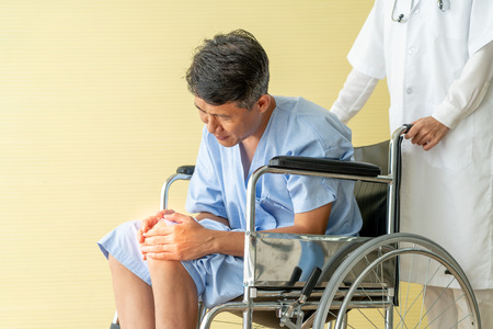 Asian senior patient wheelchair with knee pain - selective focus point Reklamní fotografie
