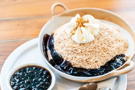 Milchtee-Eisrasur mit schwarzer Blase und schwarzem Grasgelee im Café