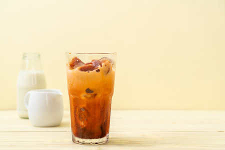 Thai tea ice cube with milk on wood background