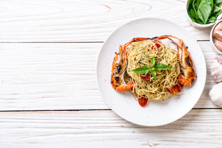 stir-fried spaghetti with grilled shrimps and tomatoes - Italian fusion food style Standard-Bild