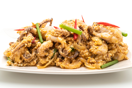 Stir-Fried Squid or Octopus with Salted Eggs isolated on white background 스톡 콘텐츠